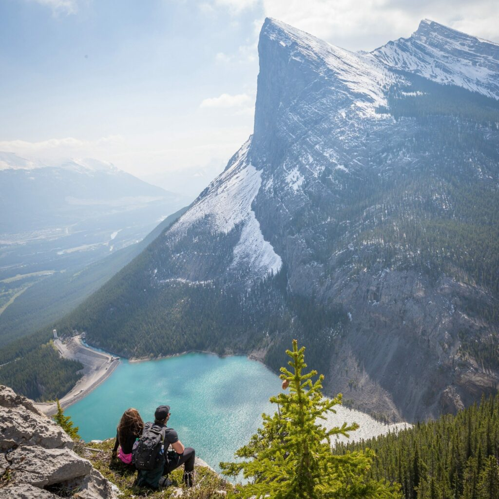 Man and woman sitting on a cliff looking at a lake and mountain