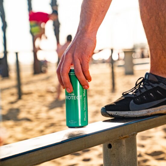 a person reaching down at the beach for a mude protect can