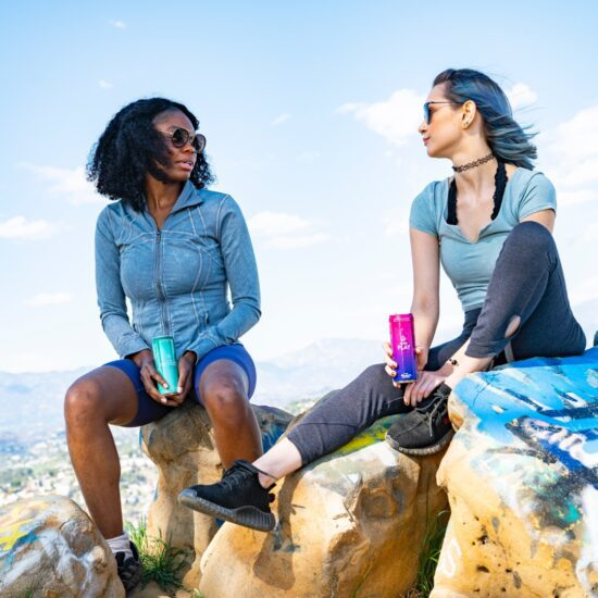 two women sitting on a cliff with two cans of mude protect and play